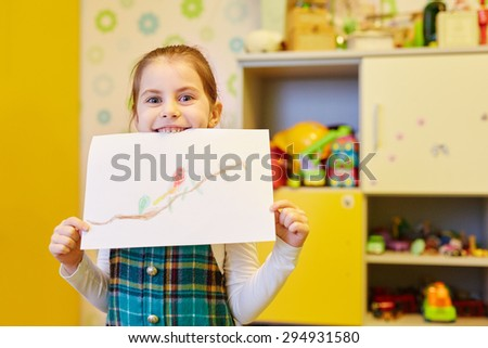 A little girl showing you the picture she'd drawn - stock photo