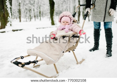A little girl sitting in childrens sled in the park. Close up. Happy family walking in the park. Portrait Infant.