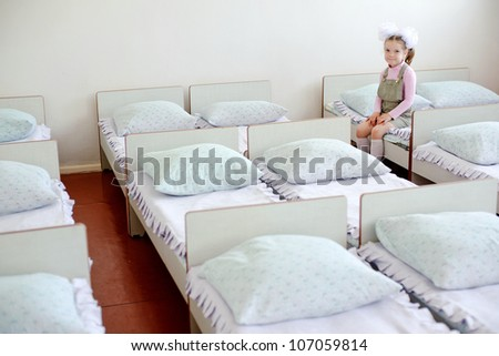 A little girl sitting on a bed in the kindergarten - stock photo