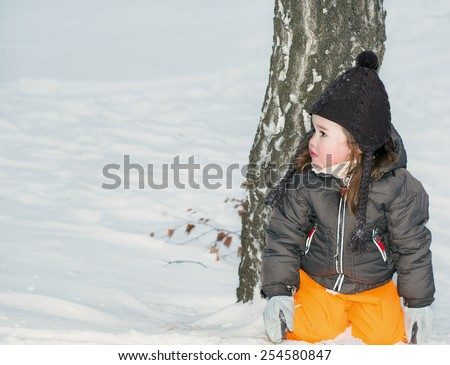 A little girl sitting on her knees in the snow
