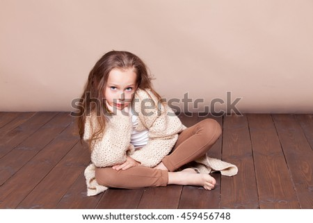 a little girl sitting on the floor and sad - stock photo