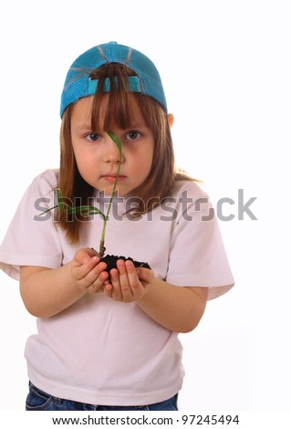 A little girl stands and holds a plant in the hands - stock photo