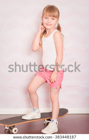 a little girl stands on skateboard on a light background