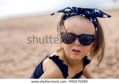 a little girl stands on the shore of the beach in a black bathing suit and black glasses - stock photo