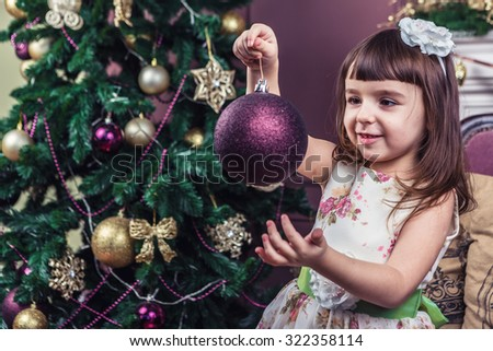 A little girl stares at the purple sphere Christmas toy decoration. Merry Christmas and happy New Year! A series of photos - stock photo