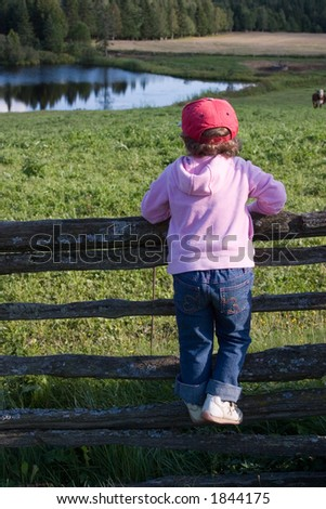 A little girl stares out over a farm field, while perched on a wood rail fence.