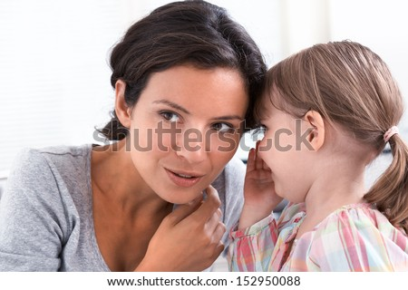 A little girl telling her mother a secret, indoor - stock photo