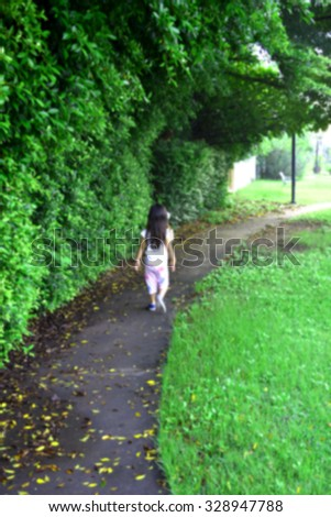 a little girl walking along greenery walkway alone