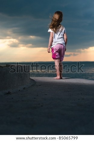 A little girl watches the approaching storm