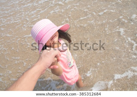 A little girl wearing a pink hat, holding his father's hand at the beach. - stock photo