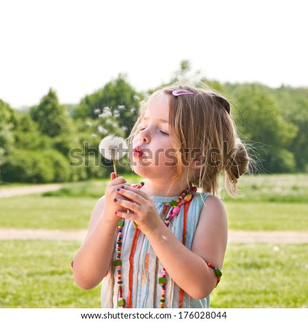 A little girl wearing colorful beads blowing the fluff off of a dandelion head. - stock photo