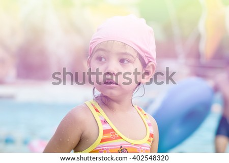 A little girl wearing swimming suit and hat at swimming pool, filtered color tone - stock photo