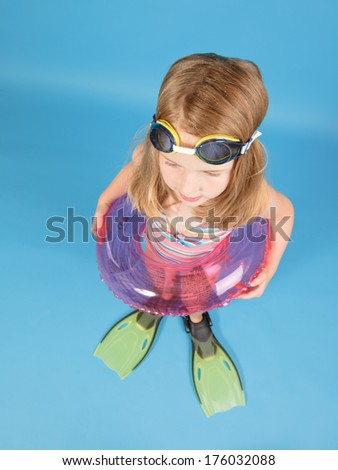 A little girl with a float and green flippers.