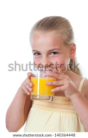 a little girl with a glass of orange juice smiling