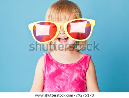 A little girl with a huge sunglasses on blue background