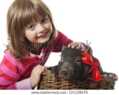 a little girl with a little black pig in a basket