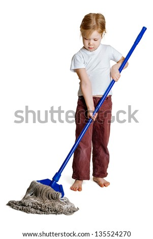 A little girl with a long mop washes the floor - stock photo