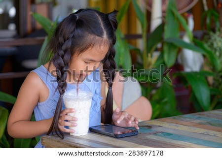 a little girl with a mobile phone on background nature. - stock photo