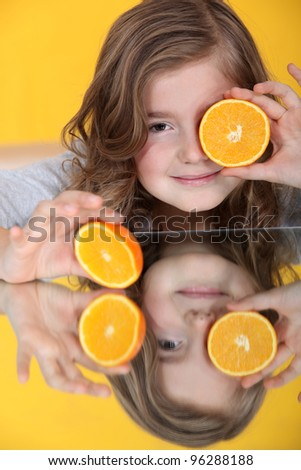 A little girl with an orange cut in half. - stock photo