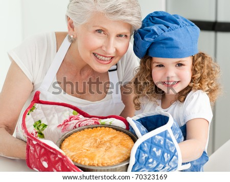 A little girl with her grandmother looking at the camera at home - stock photo