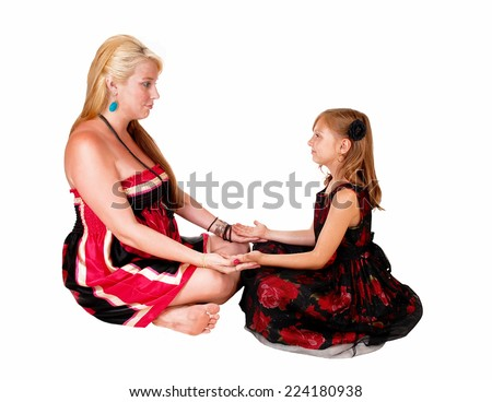 A little girl with her mom sitting on the floor and playing with each other, isolated on white background.  - stock photo