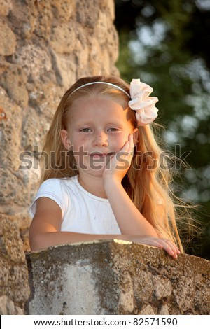 A little girl with long red hair and freckles in a stone tower on the balcony - stock photo