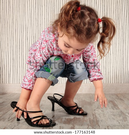a little girl with mom�´s shoes - stock photo