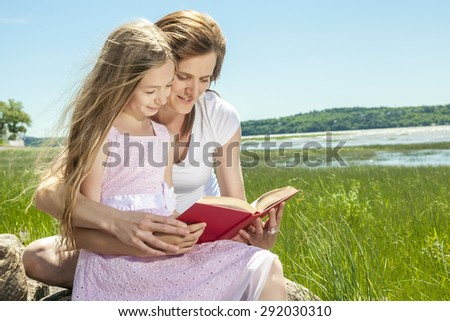 A Little girl with mother reading a book in a summer park - stock photo