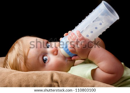 A little guy is drinking from his milk bottle very heavily. Even has a little milk drool coming out. - stock photo
