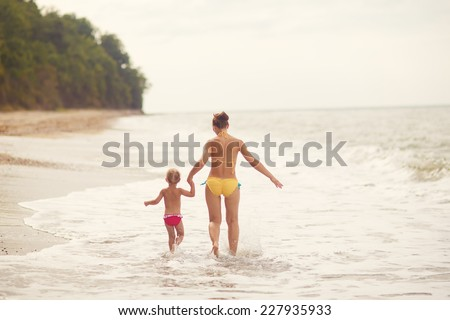 A little happy beautiful girl and her young mother in a swimsuit walking on the sea shore on a warm summer day