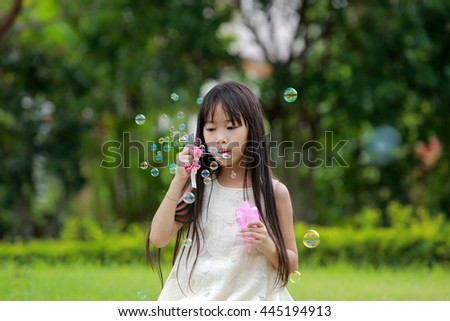 A little happy girl blowing soap bubbles in summer park.