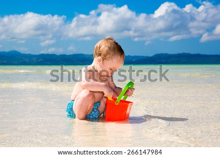 A little kid having fun on a tropical beach. Summer vacation concept.