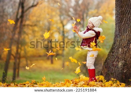 A little lovely girl in a bright red jacket and white knitted hat walking in a park on a sunny autumn day. Child playing with yellow leaves - stock photo