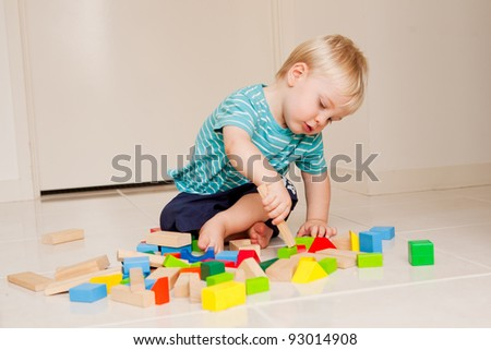 A little 15 month old boy playing with colorful blocks indoors.
