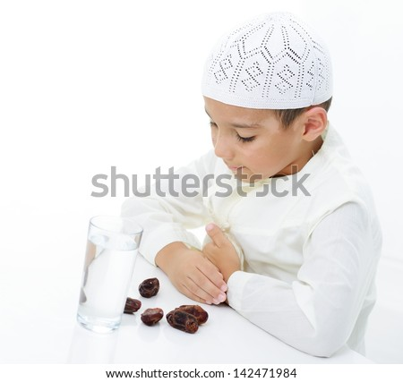 A little muslim boy wearing islamic attire ready for braking Ramadan fast - stock photo