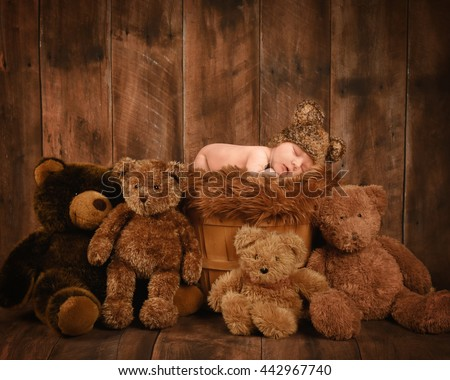 A little newborn baby is sleeping in a basket with teddy bear friends on a wood background for a love, family or photography concept.