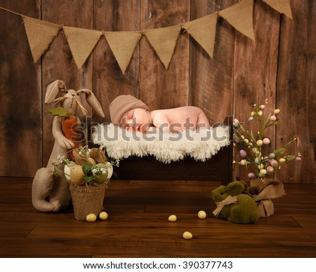 A little newborn baby is sleeping in a white fur bed on a studio rustic wood background with Easter eggs and a bunny for a holiday or love concept.