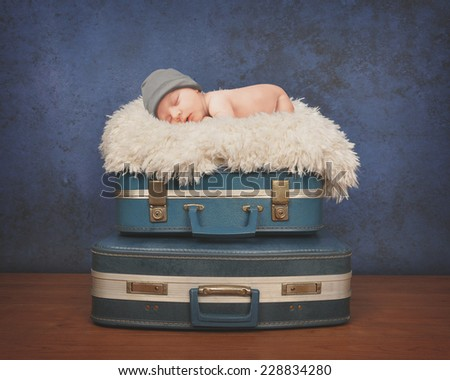 A little newborn baby is sleeping on a white fur blanket on top of blue suitcases for a travel or photography concept. - stock photo