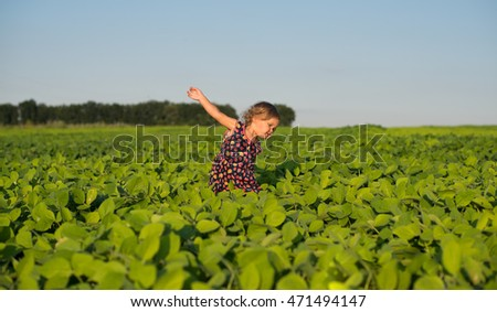 A little pretty girl in a green Bavarian dress with a apron picking flowers in the field of flowering yellow mustard on a sunny summer day. Kids and nature. Children in country. Beautiful flora