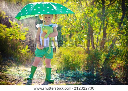 A little pretty girl in green rain boots playing with toy and umbrella in a summer park.