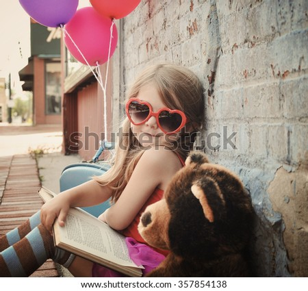 A little retro girl is wearing heart sunglasses reading a book downtown against a brick wall for a education or creative concept. - stock photo