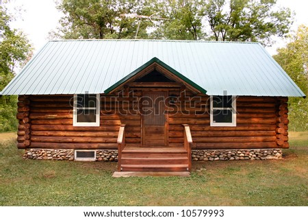 a little rustic log cabin in the woods - stock photo