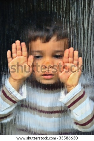 A little sad kid looking through glass