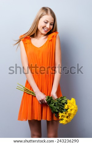 A little shy. Beautiful young woman in pretty dress holding bouquet of flowers while standing against grey background