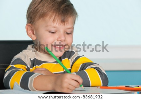 A little smiling boy draws at the desk - stock photo
