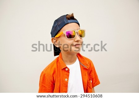 A little stylish boy in sunglasses and a blue hat posing on a white background.