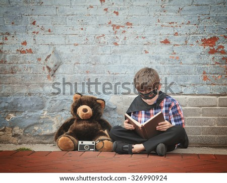 A little super hero child is reading a story book with a teddy bear and camera against an old vintage brick wall for an education or creative concept.