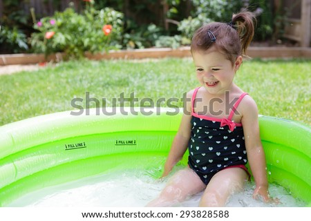 A little toddler girl in a black swimsuit playing in the pool in the garden - stock photo