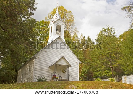 A little white country church in the beginnings of fall colors. - stock photo