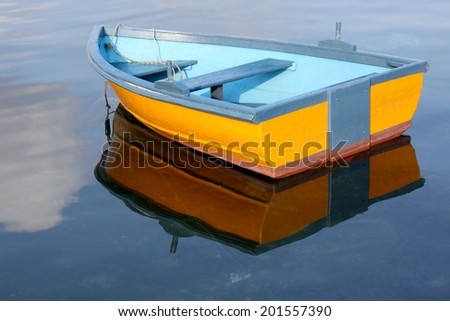 A little yellow and blue row boat floating on the water - stock photo